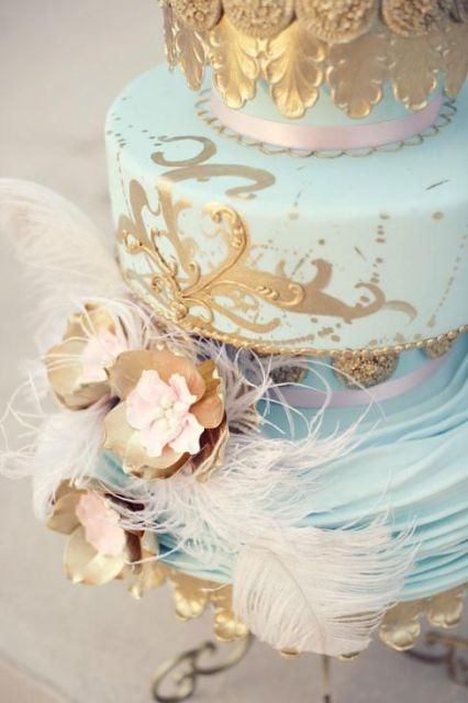 a blue wedding cake with a gold pattern, pink ribbons and sugar gold blooms and real feathers for a whimsy wedding