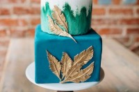 a bright square and round wedding cake in blue and teal, with gold feathers for detailing is a bold and cool idea