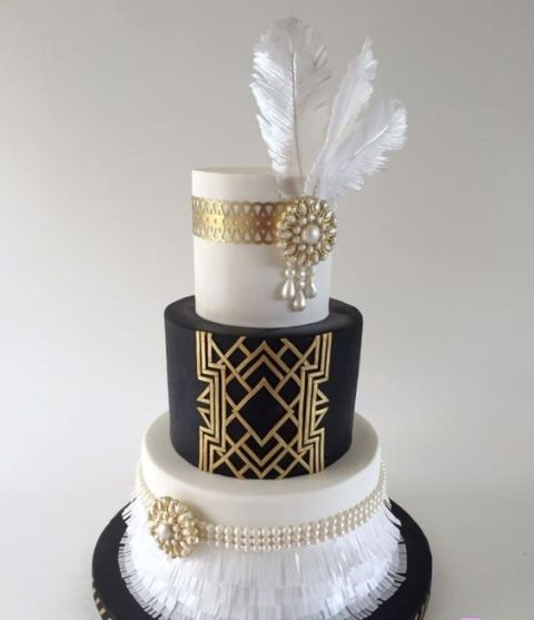 a contrasting black and white wedding cake with painted and embellished tiers, with a fringe tier and several feathers on top