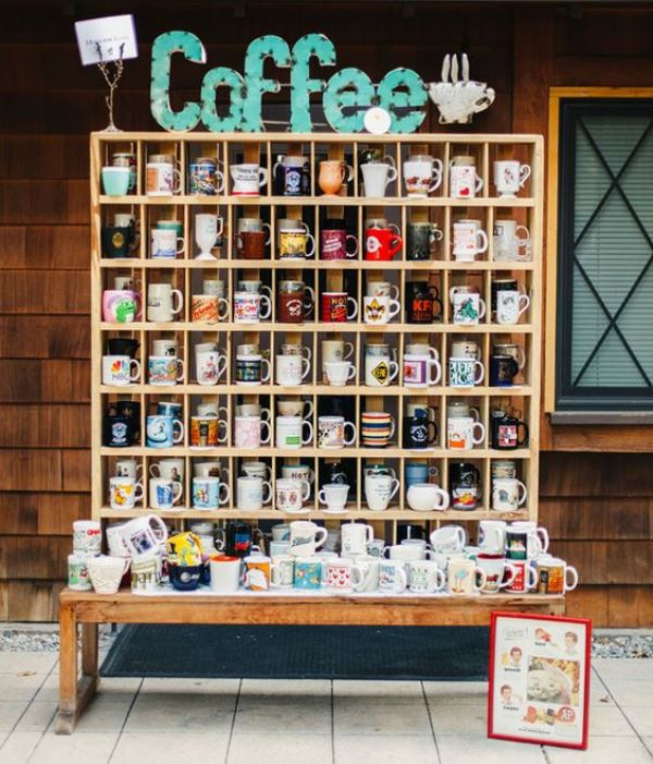 a cool coffee mug station with various mugs as wedding favors ad marquee lights is great for a coffee-loving wedding