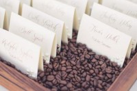 escort cards placed into a wooden box filled with coffee beans is a cool and fresh idea to display them