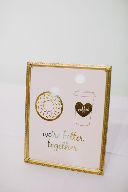 a cute wedding sign in pink and gold with a coffee cup and a donut is a fun decoration for a relaxed wedding
