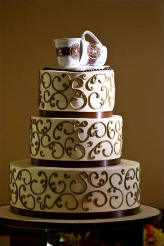 a patterned wedding cake with coffee mugs on top is amazing for a coffee-loving wedding couple
