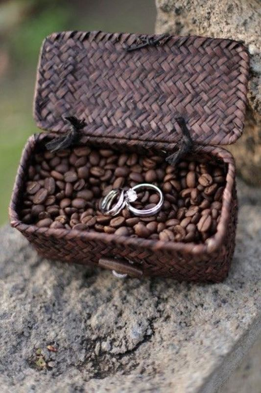 a woven basket with coffee beans and wedidng rings is a creative and cute idea to display them