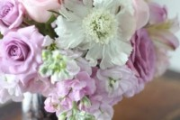 a floral centerpiece of pink and white blooms, with greenery and a sheer vase filled with coffee beans