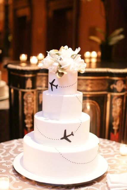 a black and white wedding cake topped with fresh blooms and with planes to mark that it's a travel-themed wedding