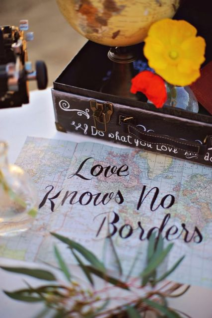a suitcase with a globe and blooms as decor and a map with a cool quote for a travel-themed wedding