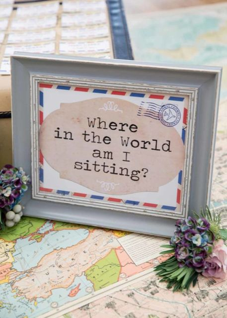 a bright sign styled as a card with a cool quote is a nice idea for a travel-themed wedding