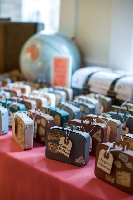 mini cardboard suitcases with favors inside are amazing for a travel-themed wedding