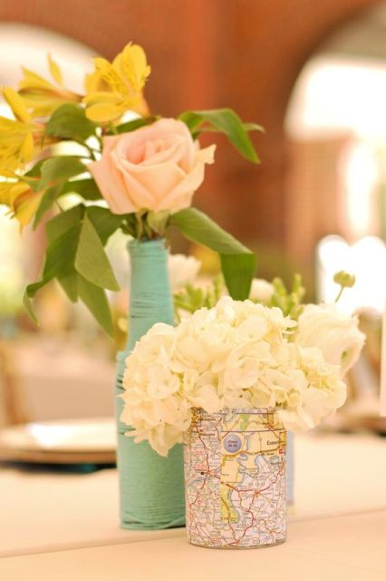 a cute wedding centerpiece of a mint vase with pink blooms and a map covered vase with white flowers for a travel-themed wedding