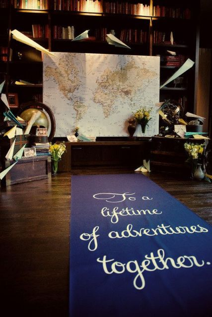 a travel-themed wedding backdrop with a map, a globe, paper air planes and flowers