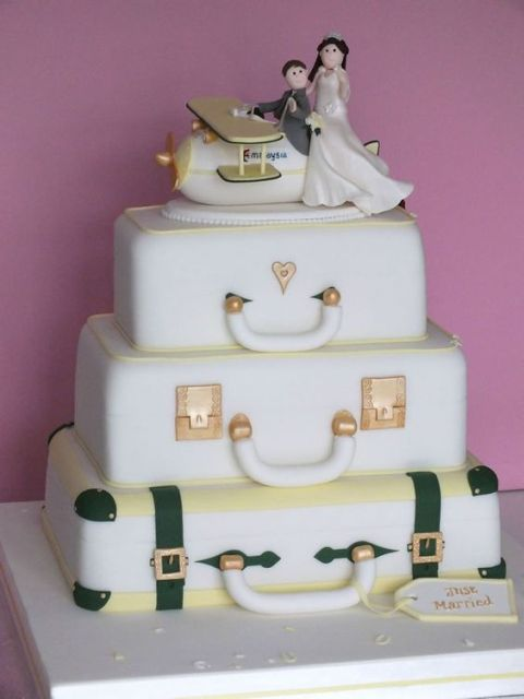 a unique wedding cake composed of suitcases and a plane with cake toppers is a fun idea for a travel-themed wedding