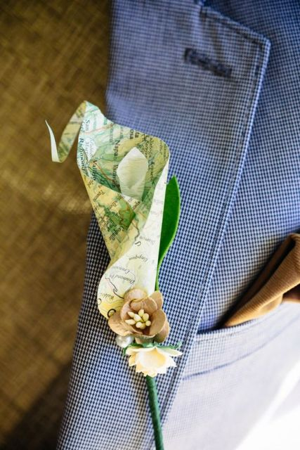a map boutonniere with fabric blooms is a cool accessory for a travel-themed wedding, for grooms and groomsmen