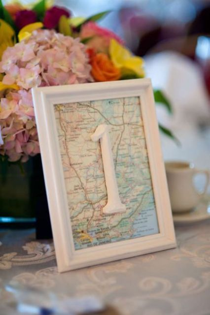 a pastel floral centerpiece and a map table number for a cool travel-themed wedding