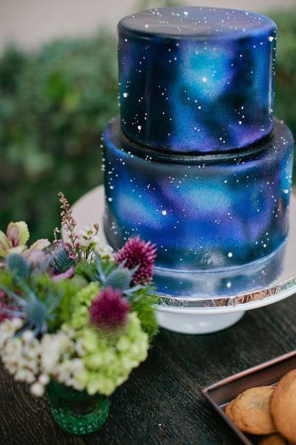 a bold galaxy-inspired wedding cake done in navy, bold blue, midnight blue and purple and accented with sparkles