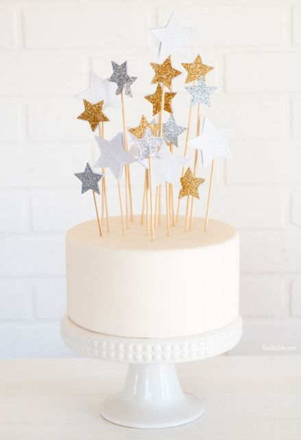 a white wedding cake topped with metallic stars of various sizes is a fun and cool idea for an astronomy wedding