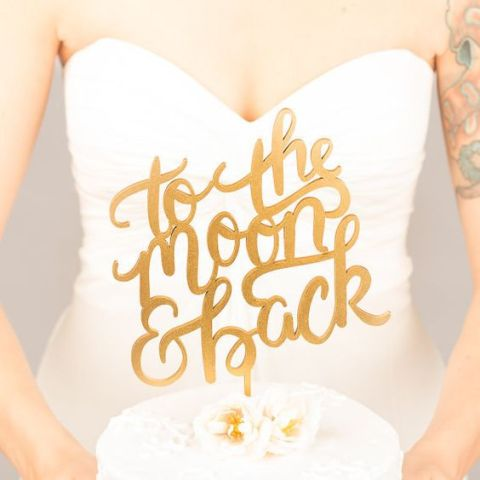 a gold calligraphy cake topper is a nice accent for your astronomy or galaxy wedding