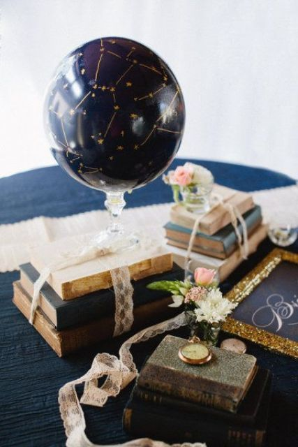 an astronomy wedding centerpiece of vintage books, blooms, a watch and a navy and gold sky globe