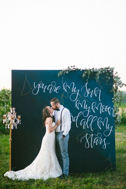 a chalkboard wedding backdrop with greenery and blooms and a quote dedicated to the galaxies and stars