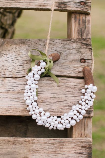 a wedding decoration of a horseshoe covered with pearls and a single bow is a cool idea for rustic weddings