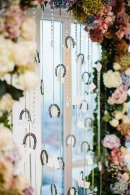 a creative seating chart of a pastel and neutral blooms arch, rhinestones and mini horseshoes that holds cards