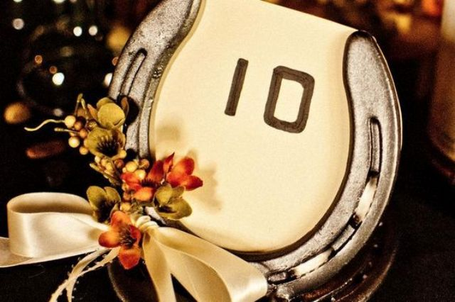 a wedding table number of a horseshoe, a number, some berries and a silk bow is great for a rustic wedding