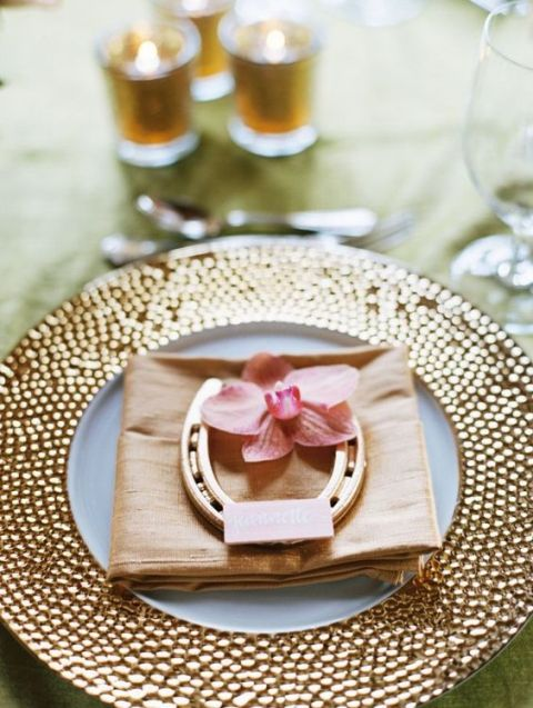 a wedding place setting with a gold charger, a neutral napkin, an orchid and a horseshoe