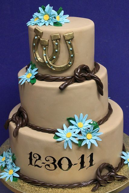 a tan wedding cake with ropes, blue blooms and gold horseshoes is a nice rustic idea