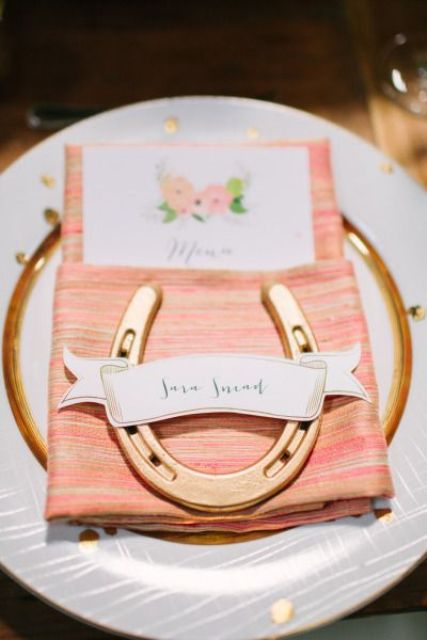 a place setting of a gold rim charger, a colorful coral napkin, a gold horseshoe and a floral card for a rustic wedding