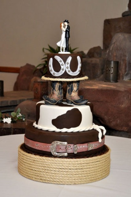a cowboy wedding cake with a hat, cow print, boots, horseshoes and a romantic couple cake topper