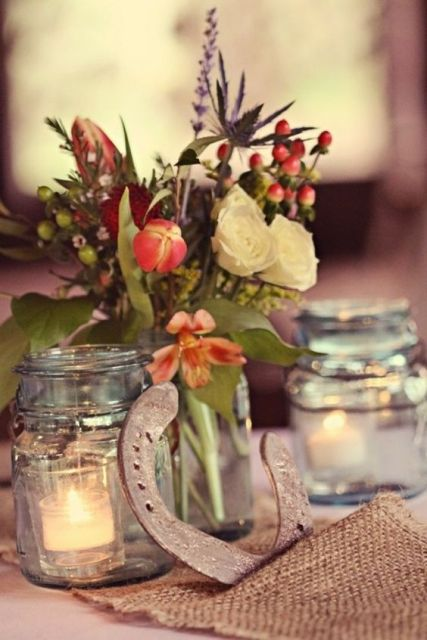 a rustic wedding centerpiece of candles in jars and a simple floral arrangement in a jar