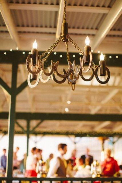 a rustic wedding chandelier of horseshoes and candles is a gorgeous idea for a rustic or cowboy wedding