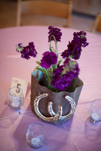a rustic wedding centerpiece of a metal vase, purple flowers and some horseshoes for a cowboy feel