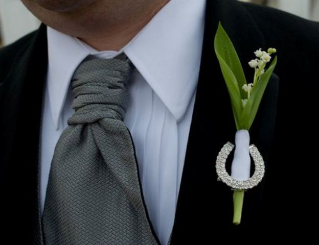 a unique and elegant wedding boutonniere of lily of the valley and a rhinestone horseshoe will fit any groom