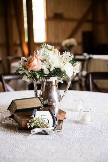 a cool wedding centerpiece of books, a horseshoe with flowers and a silver vase with white and pastel blooms