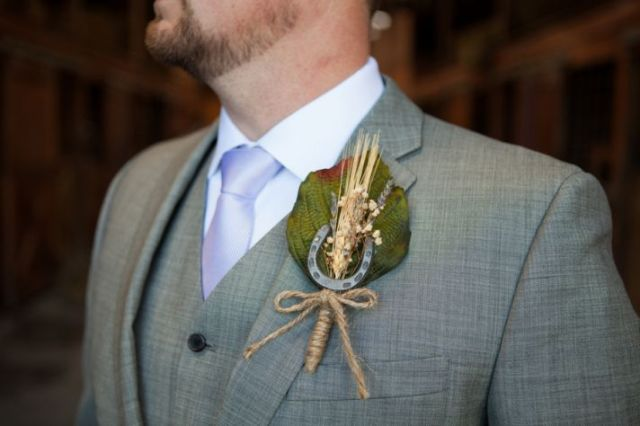 a wedding boutonniere of a leaf, a spike, baby's breath and a horseshoe and twine