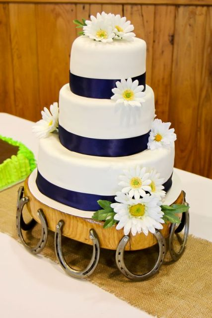 a wedding cake with navy ribbons and white blooms on a stand decorated with horseshoes for a rustic touch