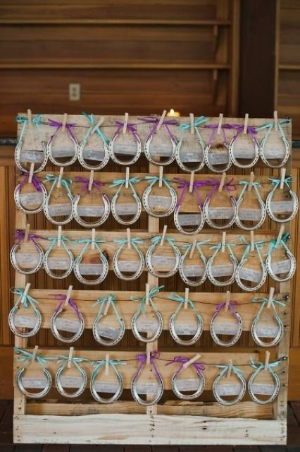 rustic wedding favors - horseshoes with turquoise and purple bows attached with clothespins to a pallet