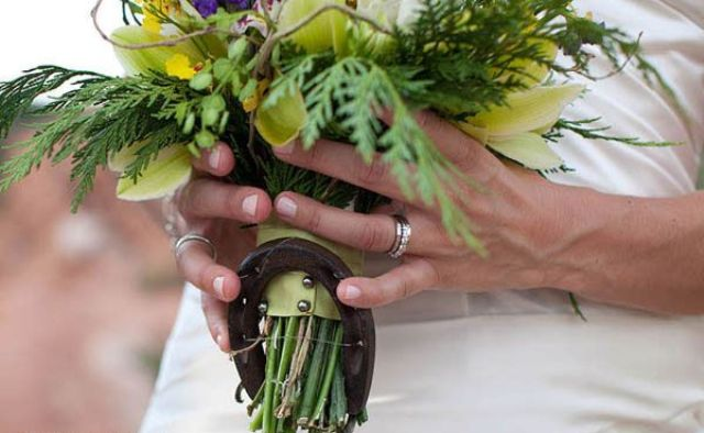 a colorful wedding bouquet accented with a single horseshoe is a creative idea for a rustic or cowboy bride