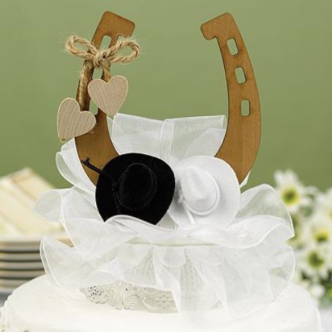 a wedding cake with a plywood horseshoe topper, hats, hearts and a large bow for a rustic wedding