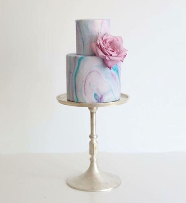 a bright marble wedding cake decorated with a single pink flower is a pretty idea for a modern pastel wedding