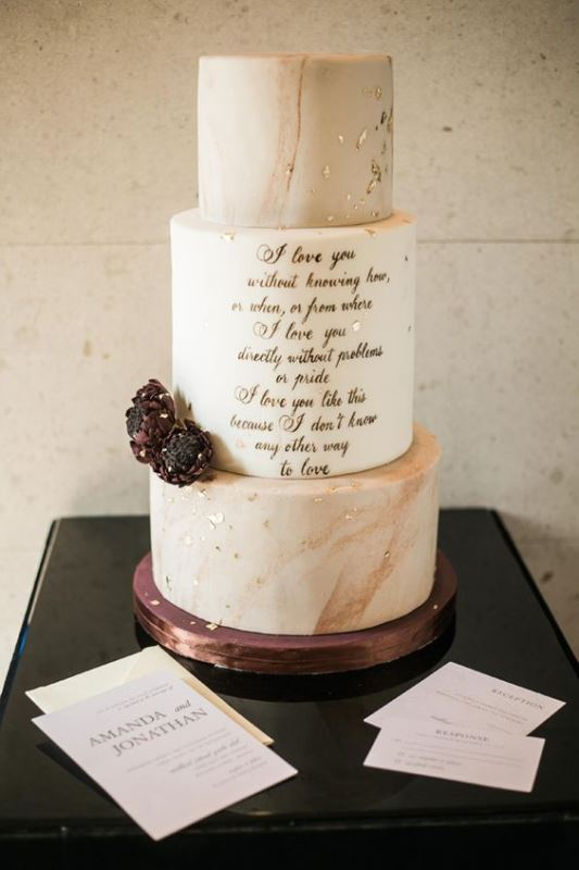 a sophisticated wedding cake with peachy marble tiers and a white one with calligraphy, gold leaf and dark blooms for a romantic wedding