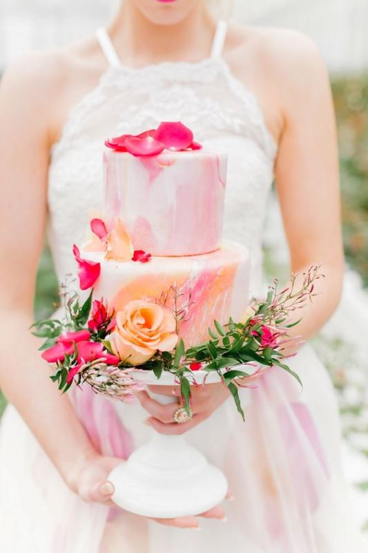 a bright pastel watercolor wedding cake decorated with pastel and bold blooms and with greenery is a gorgeous idea