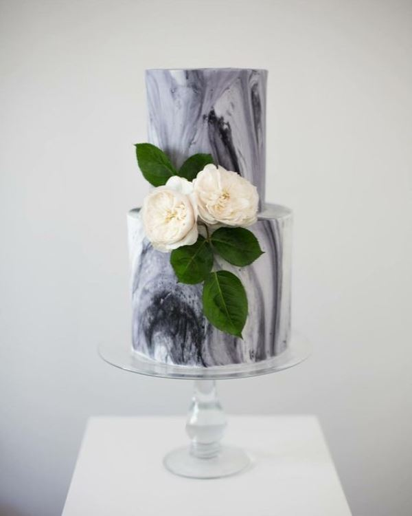 a grey marble wedding cake with white blooms and foliage is a classic idea for a spring or summer wedding