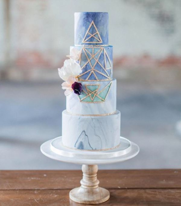 a gorgeous four-tier blue ombre marble wedding cake with gold geometric detailing and some blooms is veyr exquisite and bold