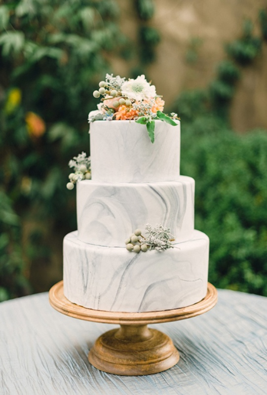 a white marble wedding cake with neutral and bold blooms and berries is classics for a summer wedding