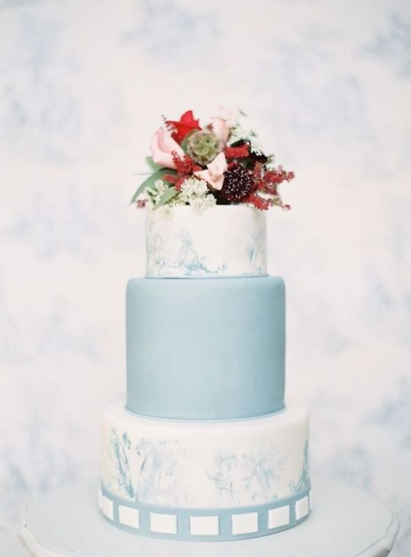 a lovely wedding cake with blue marble and a plain blue tier, bold blooms and greenery on top is chic and contrasting, great for a fall wedding