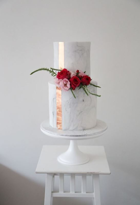 a classic white marble wedding cake with a copper ribbon and bold blooms and greenery is modern