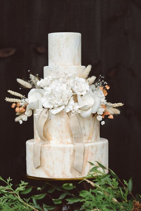 a neutral marble wedding cake with dried, fresh and sugar blooms and some ribbons is a refined wedding dessert idea