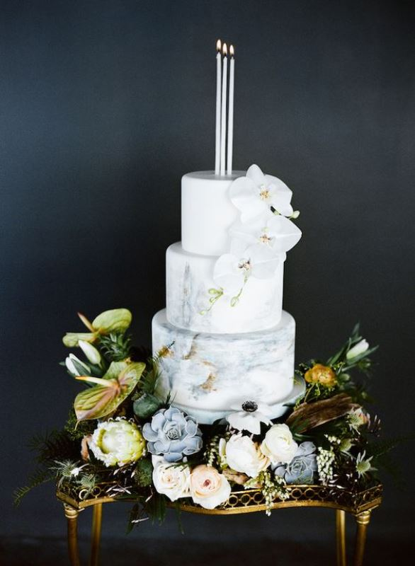 a neutral marble wedding cake decorated with candles and white orchids plus fresh blooms and succulents around is a refined out of the box idea